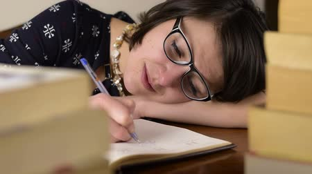 crows feet : Black glasses woman sleep work on a wood desk behind of books