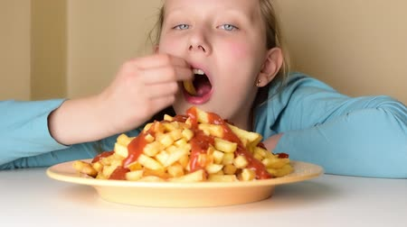 munch : Blonde hungry teenage girl looking eating  french fries from dish on table Stock Footage