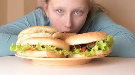 munch : Blonde hungry teenage girl looking waiting hamburger from dish on table