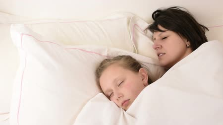 sleep : Beautiful brunette mom and blonde blue eyed daughter fall asleep on bed together Stock Footage