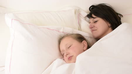 усталый : Beautiful brunette mom and blonde blue eyed daughter fall asleep on bed together Стоковые видеозаписи