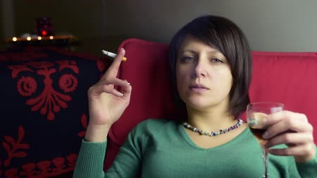crows feet : Tired pensive attractive woman smoke cigarette and drink vine  closeup Stock Footage