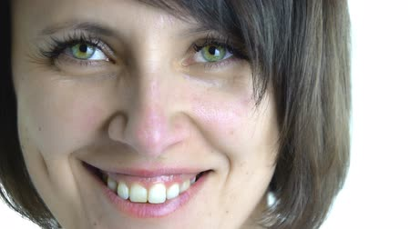 gülümseyen : Emotional states: Close up of calm and happy attractive green eyed adult woman is smiling portrait isolated Stok Video