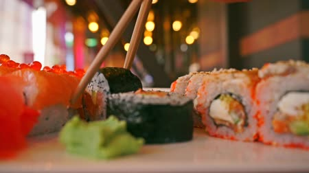 comida japonesa : Japanese food restaurant. Woman picks roll with chopsticks close up video