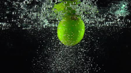 calcário : Whole lime rotating under water super slow motion shot. Black background
