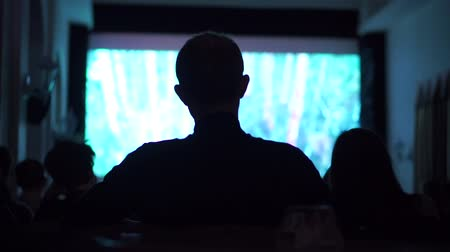 kino : Silhouette of young man watching movie in dark cinema hall