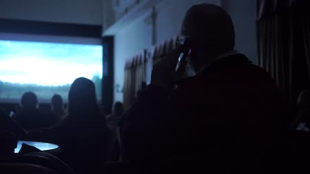sinematografi : Man talking on his cell phone in dark cinema hall violating rules