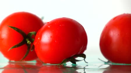отскок : Red ripe tomatoes hit wet glass surface with splashes and rebound. Slow motion