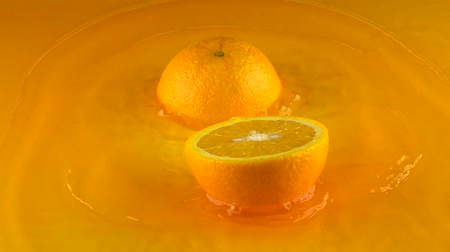 citrusové plody : Orange hits orange juice surface and splits into halves. Slow motion video