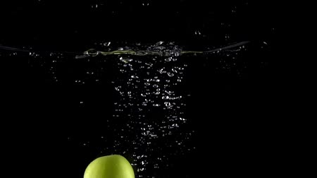 фрукты : Super slow motion shot: falling juicy green apples and splashes of water Стоковые видеозаписи