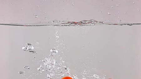 hurl : High speed camera shot: red ripe tomatoes splash in water, grey background