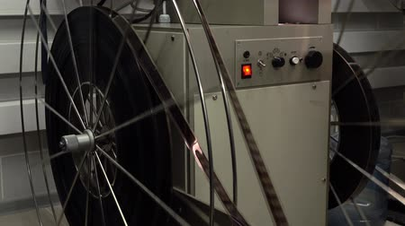 perforation : Dolly shot of big rotating reels in pro cinema projector, 4K video, part of set