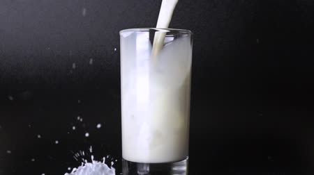 dairy animal : Pouring milk in glass against black background. 500 fps super slow motion video Stock Footage