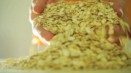yulaf ezmesi : Girl in orange clothes scooping rolled oats with her hands, slow motion video