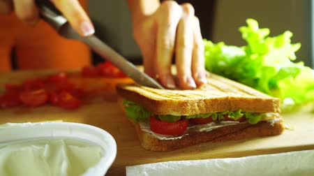 salad : Young woman splitting sandwich with a knife