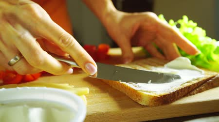 cheese piece : Making a sandwich: spreading soft cheese on a toasted bread