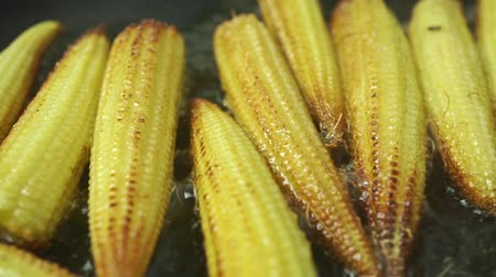 hiss : Roasting small corn cobs, macro dolly shot Stock Footage