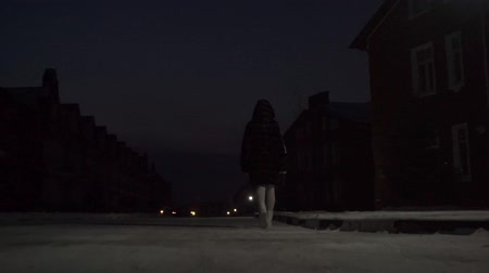 fur boots : Girl in fur coat walking in snowy residential area at night, zoom in video Stock Footage