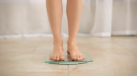 com escamas : Female Standing on Weight Scale