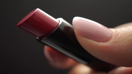 lakier do paznokci : Close up of new red lipstick in a beautiful girl hand