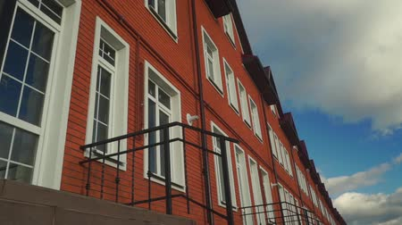 homeopático : Clouds floating above row of red brick townhouses