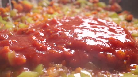 molho de tomate : Adding dense tomato sauce to roasting vegetables. Close up video