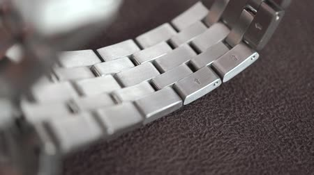 anyagi : Polished steel watch wristlet being placed on a brown surface