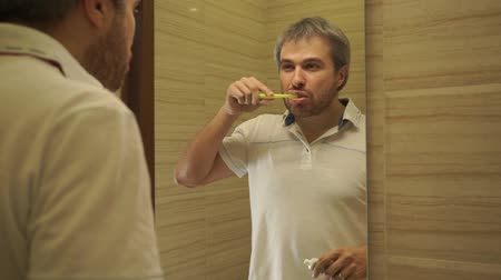 usual : A man brushing his teeth in the bathroom