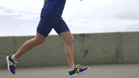 банк : Athletic man running against river bank parapet and sky. Super slow motion steadicam video 240 fps