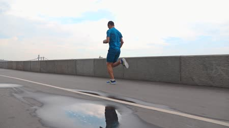 Sportsman running on river embankment after rain against parapet and sky. Slow motion steadicam video shot at 120 fps Stok Video