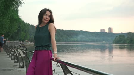 único : Romantic brunette girl standing on park embankment at evening. Slow motion shot Vídeos