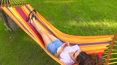 гамак : Slender pretty brunette laying in bright hammock and using her mobile phone, view from above. 4K shot Стоковые видеозаписи