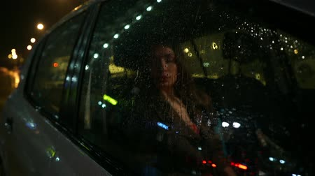 reflexão : Beautiful brunette girl behind car window at rainy night Vídeos