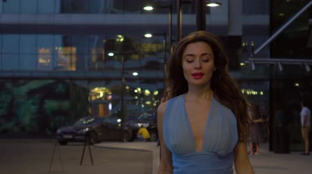 večer : Beautiful brunette girl in blue dress walking on the street at night, 4K clip