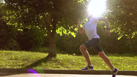 rotaları : Steadicam tracking video of athletic man in white tshirt running in park against sun and trees, super slow motion, 240 fps