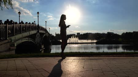 make photo : Slender brunette girl in sunglasses taking photo of big park fountain with her mobile phone. 4K shot