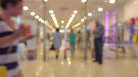 Unrecognizable customers walking in modern shopping mall. 4K bokeh shot Stok Video