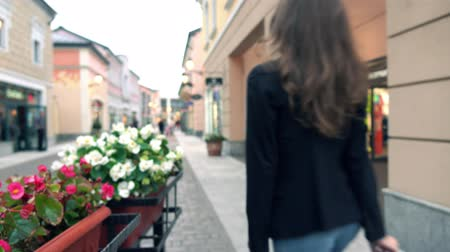 magro : Offuscata ragazza bruna sottile in jeans cammina con le sue purchasings in sacchi vicino outlet. video di sfondo bokeh 4K