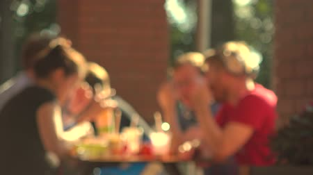 unrecognizable people : Blurred young people eating fast food outdoor. 4K background bokeh video Stock Footage