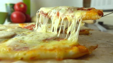pieces of cheese : Cooking, part of the set. Taking a piece of freshly baked homemade pizza with stretching cheese. 4K close up video Stock Footage
