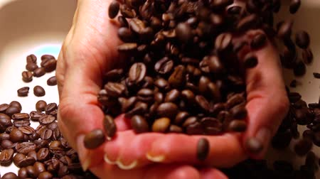 кофе : Pouring coffee beans into woman hands, super slow motion shot
