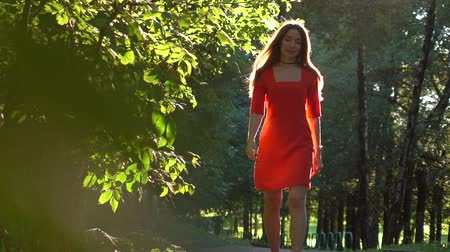 delgado : Pretty caucasian brunette girl in red dress walking along sunny park alley. Slow motion video