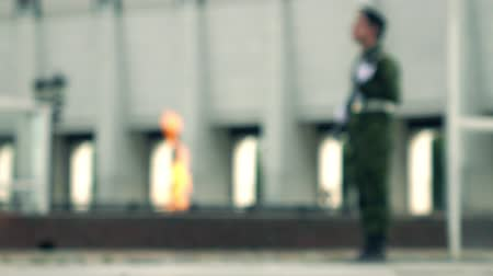 muhterem : Defocused eternal flame memorial and armed guard. 4K bokeh background video