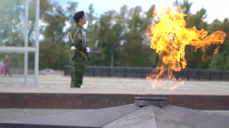 muhterem : Memorial fire and armed guard wearing camouflage. Super slow motion long shot