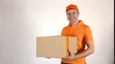 перевозка груза : Delivery man in orange uniform delivering a big box. Light gray backround, 4K studio shot