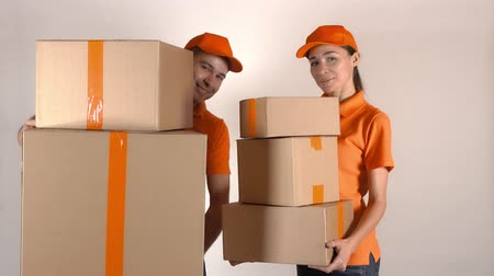 posta kutusu : Male and female couriers in orange uniform delivering multiple cartons. Light gray backround, 4K studio shot Stok Video