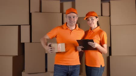 kurier : Couriers in orange uniform standing against brown carton stacks backround. Delivery company staff. 4K studio video Wideo