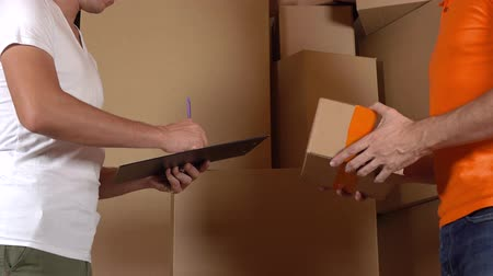 Store assistant in orange uniform giving a box to a customer. Cartons background, 4K studio shot