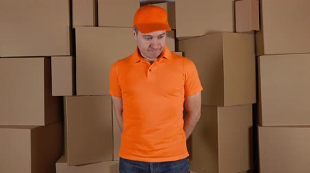 paket : Courier in orange uniform delivering damaged parcel to customer. Brown cartons background. Flaw and unprofessional work concepts. 4K studio shot Stok Video