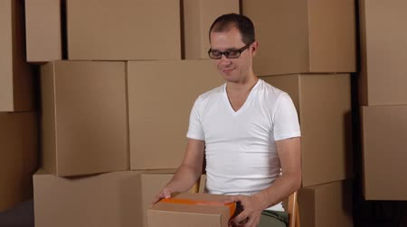 self storage : Young geeky owner of small internet store holding parcel against carton stacks. 4K clip Stock Footage